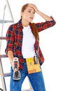 Worried diy handy woman standing with her hand to her forehead and a wide eyed expression holding an electric drill and wearing a Stock Photos