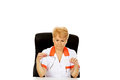 Worried elderly female doctor or nurse sitting behind the desk and holds two pair of glasses Royalty Free Stock Photo