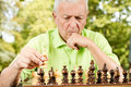 Worried elderly man playing chess outdoors Stock Photography