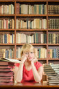 Worried female student in library with elbows on the table a shot of and bookshelf background Stock Image