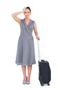 Worried gorgeous woman with suitcase posing on white background Royalty Free Stock Photography