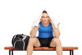 Worried male sportsman sitting on a bench isolated white background Stock Photo