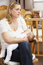 Worried Mother Breastfeeding Baby In Nursery Stock Image