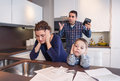 Worried mother suffering while father scream sad son and furious in a home kitchen by economic difficulties family problems Stock Photos