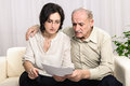 Worried old man financial problem adult daughter helping senior father looking at bad contract or expensive bills Royalty Free Stock Image