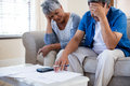 Worried senior couple checking bills in living room Royalty Free Stock Photo