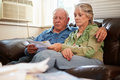 Worried senior couple sitting on sofa looking at bills home Stock Photos