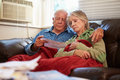 Worried senior couple sitting on sofa looking at bills whilst trying to keep warm under red blanket Stock Images
