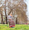 Worried senior sitting in a wheelchair in park shot with tilt and shift lens Stock Photos