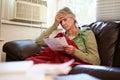 Worried Senior Woman Sitting On Sofa Looking At Bills Royalty Free Stock Photo