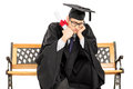 Worried student in graduation gown on bench holding diploma seated isolated white background Stock Photography
