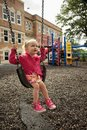 Worried swinger young girl with look on a swing in the playground Royalty Free Stock Images