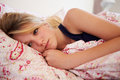 Worried teenage girl lying in bed looking away from camera Royalty Free Stock Photography