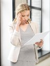 Worried woman with documents indoor picture of Stock Image