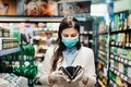 Worried woman with mask groceries shopping in supermarket looking at empty wallet.Not enough money to buy food.Covid-19 quarantine Royalty Free Stock Photo