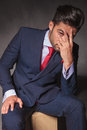 Worried young business man sitting while holding his hand on his face Stock Photos