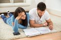 Worried young couple calculating their bills at home lying on carpet Stock Photo