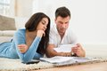 Worried young couple calculating their bills at home lying on carpet Royalty Free Stock Images