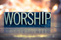 Worship concept metal letterpress type the word written in vintage on a soft backlit background Royalty Free Stock Photos