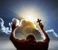 Worship love and spirituality praying man lifts his hands in prayer holds a cross to heaven with heavenly sunset through a Royalty Free Stock Photo