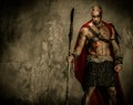Wounded gladiator holding spear in red coat Royalty Free Stock Image