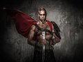 Wounded gladiator holding sword covered in blood with both hands Stock Photography