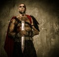 Wounded gladiator holding sword covered in blood with both hands Royalty Free Stock Image