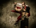 Wounded gladiator holding sword with two swords covered in blood Royalty Free Stock Photo