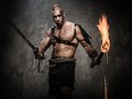 Wounded gladiator holding torch and sword covered in blood Stock Photos