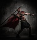 Wounded gladiator with spear in red coat throwing Royalty Free Stock Image