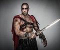 Wounded gladiator with sword covered in blood on grey Stock Photos