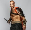 Wounded gladiator with sword covered in blood isolated on grey Royalty Free Stock Photography