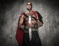 Wounded gladiator with sword holding covered in blood both hands Royalty Free Stock Photos