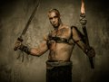Wounded gladiator with sword holding torch and covered in blood Royalty Free Stock Photos