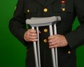 Wounded soldier veteran in class a uniform with crutches Royalty Free Stock Photography