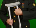 Wounded soldier veteran in class a uniform with crutches Stock Images