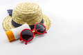 Woven hat red sunglasses with body lotion on white background Stock Image