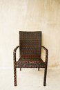 Woven plastic chair beside the concrete wall Royalty Free Stock Photos