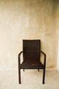 Woven plastic chair beside the concrete wall Royalty Free Stock Photo
