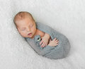 Wrapped sleeping baby with opened mouth holding little toy Royalty Free Stock Photo