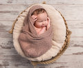 Wrapped sleepy baby with folded legs and hands on head Royalty Free Stock Photo