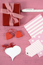 Wrapping happy valentines day gifts with gift tags and hearts on shabby chic pink background vertical Stock Image