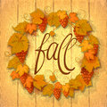 Wreath of autumn grape leaves on a dark wood background with copy space for the inscription in the center and in the