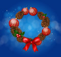 Wreath of cones and christmas bulbs on blue shiny background Royalty Free Stock Photo