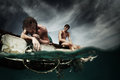 Wreck two men floating in a sea with sad faces and wounds on a body Royalty Free Stock Photo