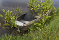 Wrecked row boat in pond