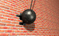 Wrecking ball hitting wall a regular metal attached to a chain and breaking a face brick Royalty Free Stock Image