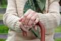 Wrinkled hands close up of holding a cane Royalty Free Stock Image