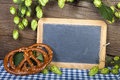 Writable slate blackboard blank with hops and two pretzels in front of a rustic brown wooden wall Royalty Free Stock Photography
