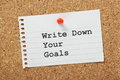 Write down your goals typed on a scrap of paper pinned to a cork notice board writing helps to make them more real and Royalty Free Stock Photography